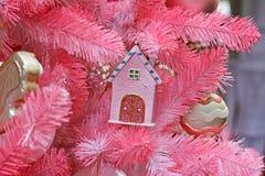 Leksakhus som hänger på filialen av den rosa julgranen Royaltyfria Bilder