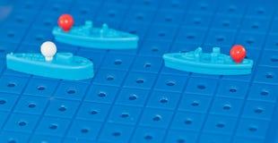 Leksakkrigskepp och en ubåt ställde upp för att spela en brädelek Arkivbilder