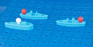 Leksakkrigskepp och en ubåt ställde upp för att spela en brädelek Royaltyfria Bilder