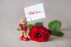 Leksaknallebjörn med en anmärkningsförälskelse och en röd ros Arkivbild