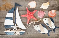 Leksaksegelbåt och fisk med snäckskal och sjöstjärna royaltyfria bilder