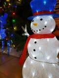 Leksaksnögubbe nära en julgran arkivbilder
