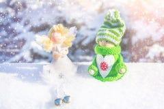 Leksakträflicka i skandinavisk stil i stucken gräsplankläder på snön och ängeln toys för spheres för bakgrundsjul exponeringsglas Royaltyfria Foton