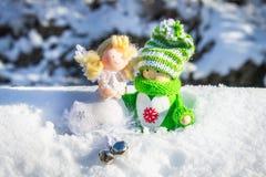 Leksakträflicka i skandinavisk stil i stucken gräsplankläder på snön och ängeln toys för spheres för bakgrundsjul exponeringsglas Royaltyfri Foto
