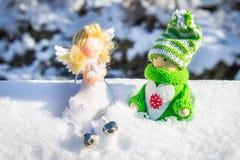 Leksakträflicka i skandinavisk stil i stucken gräsplankläder på snön och ängeln toys för spheres för bakgrundsjul exponeringsglas Royaltyfria Bilder