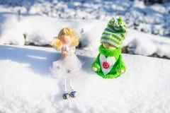 Leksakträflicka i skandinavisk stil i stucken gräsplankläder på snön och ängeln toys för spheres för bakgrundsjul exponeringsglas Arkivbilder