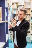 Lektor oder Bibliothekar mit Buch vor einem Regal lizenzfreie stockfotos
