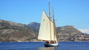 Lelantina leaving. Classic sailing yacht Lelantina leaving a bay under sail pushed by a gentle breeze Royalty Free Stock Images