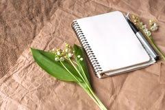 Lelie van valleien, lege blocnote en pennen op jutetextuur royalty-vrije stock afbeeldingen