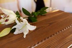 Leliebloem op houten doodskist bij begrafenis in kerk royalty-vrije stock foto's