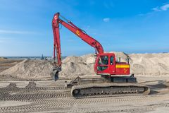 Excavator at construction site for building a new Dutch harbor. Lelystad, The Netherlands - February 02, 2018: Crane operator in excavator at construction site stock photography