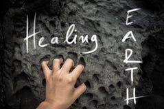 Lema de la escritura de la tierra de la cura en una foto imágenes de archivo libres de regalías