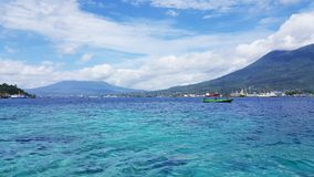 Lembeh Strait, Indonesia. Blue clear crystaline sea water in Lembeh Strait, North Sulawesi, Indonesia. Mountains and harbors at Bitung City in distance Stock Images
