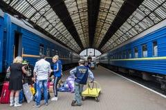 LEMBERG, UKRAINE - 21. AUGUST 2015: Das Leuteerhalten bereitete vor sich, einen Zug auf den Plattformen von Lemberg-Bahnstation z Stockfotografie