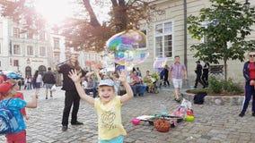 Lemberg, Ukraine - 16. Juli 2019: Kleine europäische Kinder sind, spielend springend, lächelnd und mit den Seifenblasen in einem  stock video