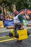 LEMBERG, UKRAINE - JULI 2016: Mächtiger starker Athletenbodybuilderstarker mann trägt schwere Eisenkoffer auf der Straße vor enth Stockbilder