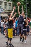 LEMBERG, UKRAINE - JUNI 2016: Basketball-Spieler spielen auf dem Quadrat im Straßenbasketball, streetball springendes Kämpfen für Stockbild