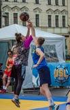 LEMBERG, UKRAINE - JUNI 2016: Basketball-Spieler spielen auf dem Quadrat im Straßenbasketball, streetball springendes Kämpfen für Stockbilder