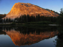 Lembert Dome at sunset. Lembert Dome in Tuolumne Meadows lit by alpenglow and reflected in the river Stock Photography