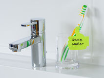 Lembrete para salvar a água no banheiro imagem de stock
