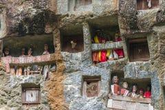 Lemo,印度尼西亚- 2014年9月5日:有在洞安置的棺材的著名掩埋处被雕刻入岩石,守卫由雕象 库存照片