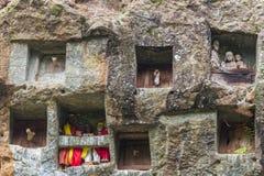 Lemo,印度尼西亚- 2014年9月5日:有在洞安置的棺材的著名掩埋处被雕刻入岩石,守卫由雕象 图库摄影
