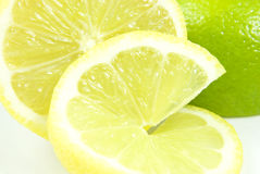 Lemon. Close-up of a lemon slice in front of lemon and lime halves Stock Image