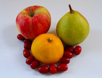 Lemon, apple, pear and dogwood berries on white tray closeup Royalty Free Stock Photos