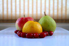 Lemon, apple, pear and dogwood berries on white tray closeup Stock Photo