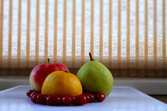 Lemon, apple, pear and dogwood berries on white tray closeup Stock Image