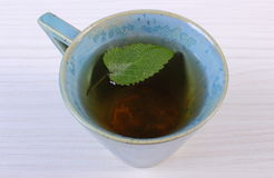 Lemon balm in cup of herbal drink on white wooden table Stock Photo