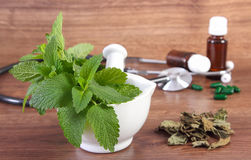 Lemon balm in mortar, stethoscope and medical capsules, choice between pills and alternative medicine Royalty Free Stock Photography