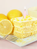 Lemon Birthday Cake with Lit Candle. Lemon birthday cake with one lit candle, lemons, and fork, on a pink background Royalty Free Stock Photos