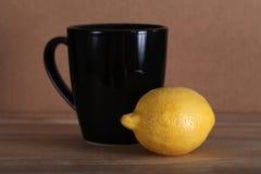 Lemon and black mug Stock Image