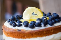 Lemon blueberry naked cake with blueberries on the top and mascarpone butter frosting. In the industrial background, detail view Stock Photography