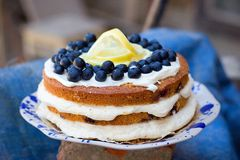 Lemon blueberry naked cake with blueberries on the top and mascarpone butter frosting Royalty Free Stock Image