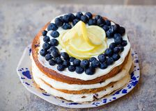 Lemon blueberry naked cake with blueberries on the top and mascarpone butter frosting Royalty Free Stock Photography