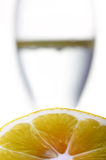 Lemon with blurred glass in background Royalty Free Stock Photography