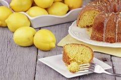 Lemon Bundt Cake. Slice of moist lemon bundt cake with real lemons in background. Shallow depth of field Stock Photography