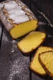 Lemon cake on corn flour with lemon liqueur. Lemon cake on the corn flour with lemon liqueur on the dark wooden background Stock Image