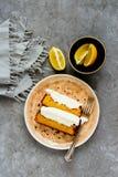 Lemon cake dessert. Flat-lay of sliced freshly baked lemon cake dessert with mascarpone cream in plate over grey concrete background top view - Image royalty free stock image