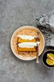 Lemon cake dessert. Flat-lay of sliced homemade lemon cake dessert with mascarpone cream in plate over grey concrete background top view - Image royalty free stock photos