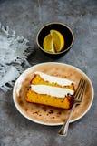 Lemon cake dessert. Sliced freshly baked lemon cake dessert with mascarpone cream in plate over grey concrete background close up - Image stock images