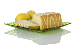 Lemon cake on glass plate, lemons in background. Lemon cake and two slices on green glass plate, lemons in background, isolated on white background Stock Photo