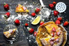 Lemon cake with strawberries, sugar end chocolate. Over an old wooden table with decorative napkins Stock Photography