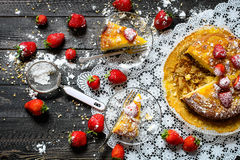 Lemon cake with strawberries, sugar end chocolate. Over an old wooden table with decorative napkins Stock Images