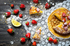 Lemon cake with strawberries, sugar end chocolate. Over an old wooden table with decorative napkins Royalty Free Stock Photos