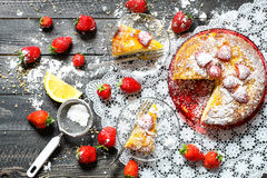 Lemon cake with strawberries, sugar end chocolate. Over an old wooden table with decorative napkins Royalty Free Stock Images