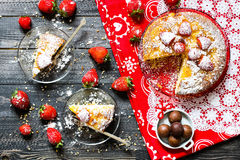 Lemon cake with strawberries, sugar end chocolate. Over an old wooden table with decorative napkins Royalty Free Stock Image