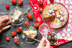 Lemon cake with strawberries, sugar end chocolate. Over an old wooden table with decorative napkins Royalty Free Stock Photography